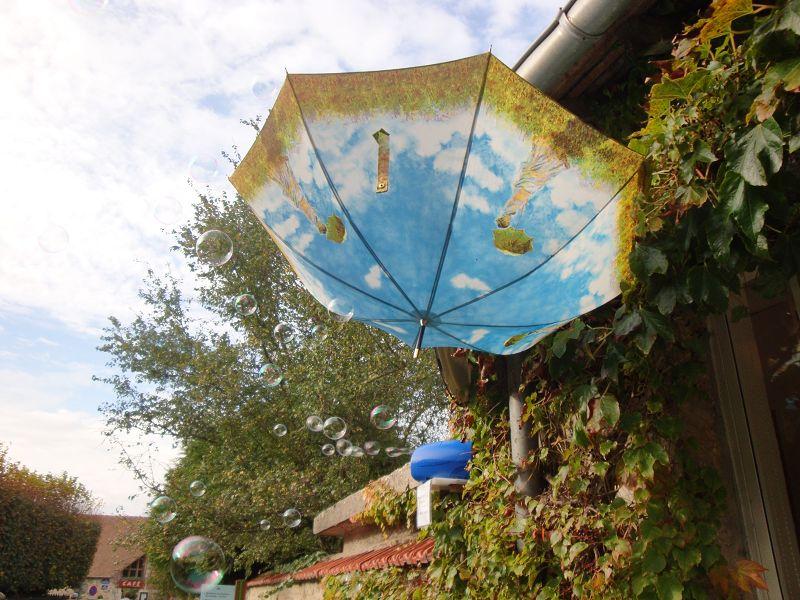 Ein Regenschirm an der Hauswand umspielt von Seifenblasen.