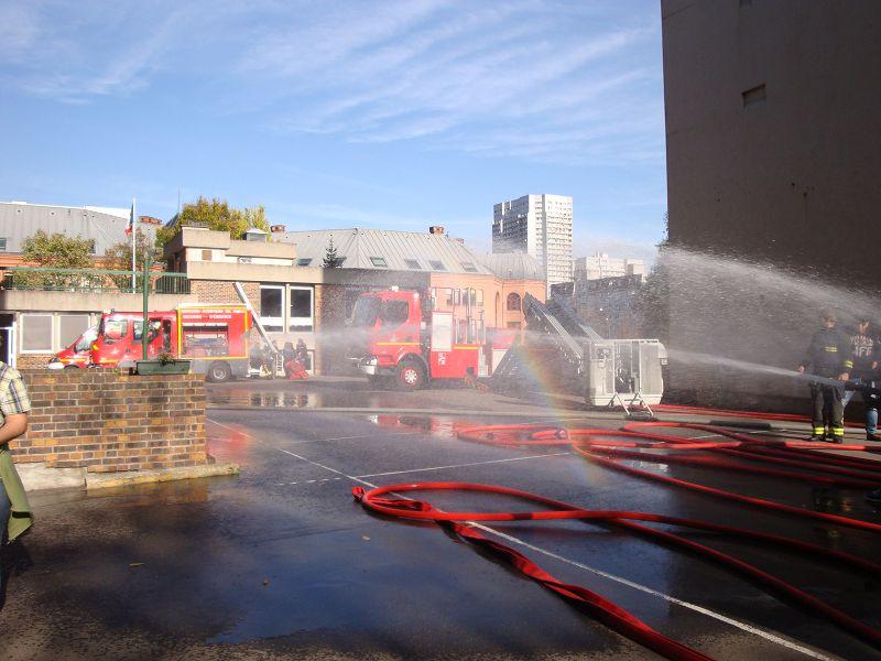 Das Sprühwasser der Feuerwehr lässt einen Regenbogen erscheinen.